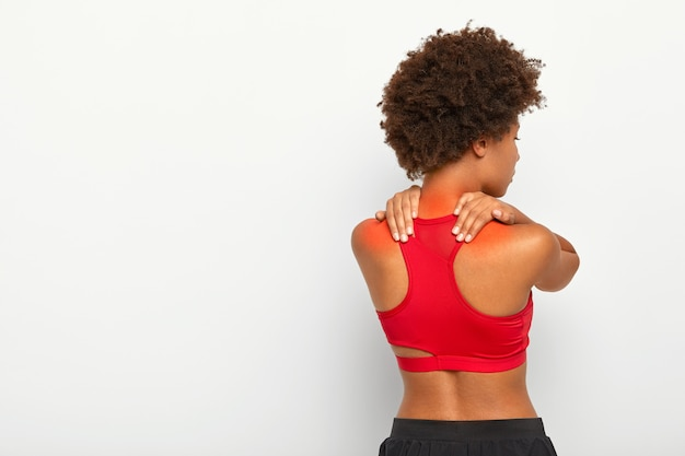 Back view of young curly woman suffers from neck pain and osteoporosis, has painful feelings in muscles, holds hands near shoulders, wears red top