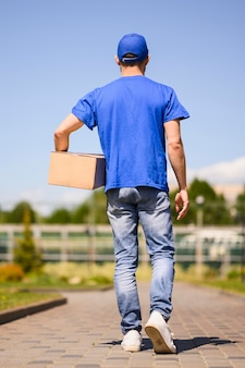 Back view young delivery man carrying parcel