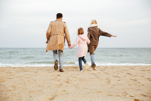 Back view of a young family with a little daughter having fun at the beach together and running