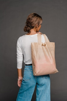 Back view of young female in casualwear holding nude beige tote bag on shoulder while standing in isolation