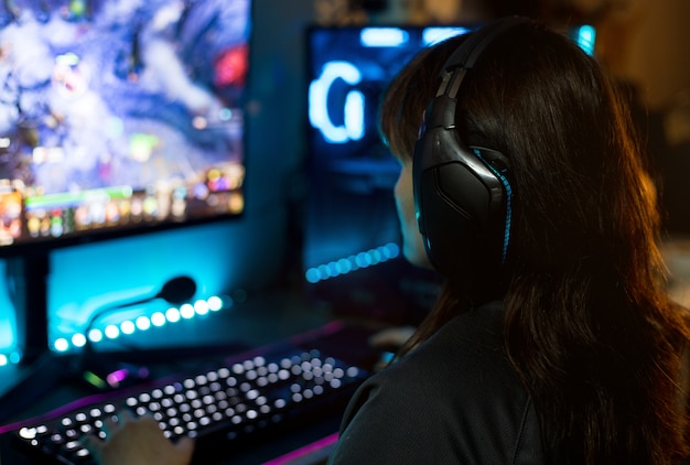 Back view of young female gamer playing video games at home