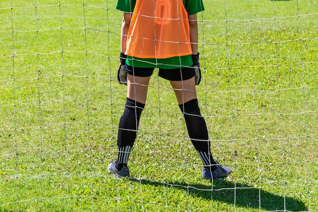 Back view of a young female goalie stading waiting in front of her goal