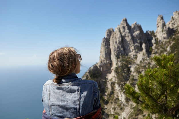 Back view of young female wearing denim jacket and sunglasses standing on top of mountain, admiring magnificent seascape and panoramic view of ai-petri cliffs while traveling alone. crimean nature.