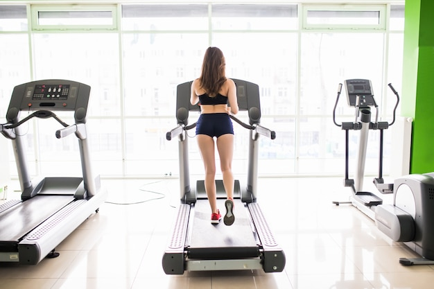 Back view of young fit woman works run on sport simulator in black sportswear and red sneakers