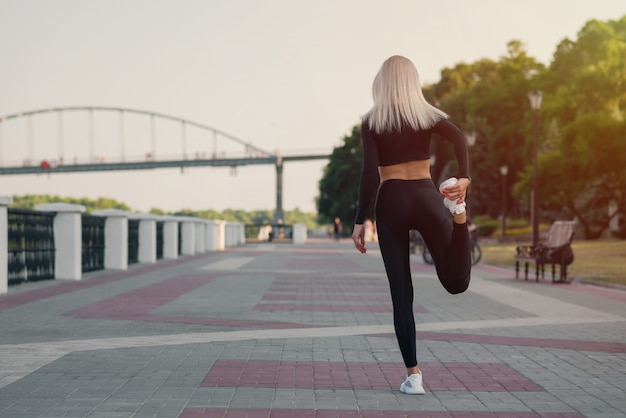 Back view of a young fitness woman runner stretching legs before run outdoors