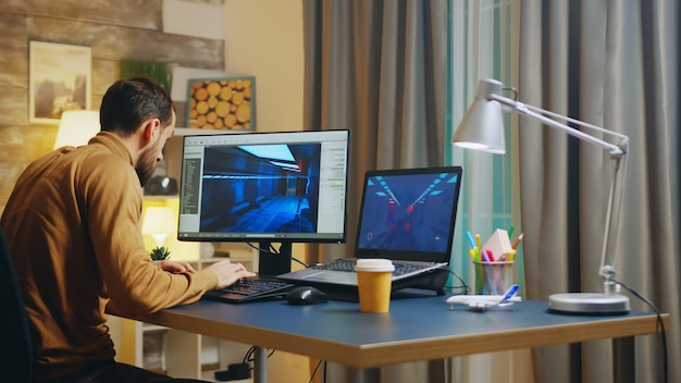 Back view of of young game developer in his home office working on graphics of the interface.