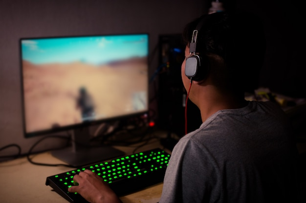 Back view of young gamer playing video games at home
