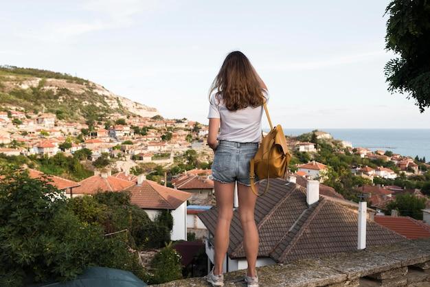 Молодая девушка, наслаждаясь отпуском, вид сзади