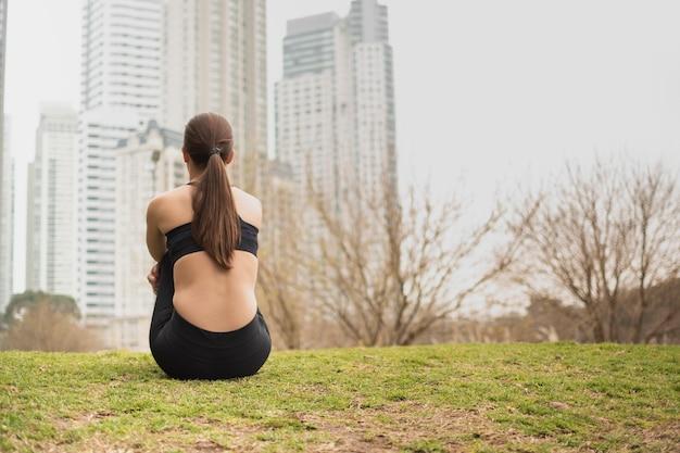 草の上に座っている若い女の子の背面図
