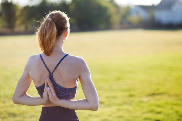 Back view of young girl in yoga position meditates in field at sunrise.