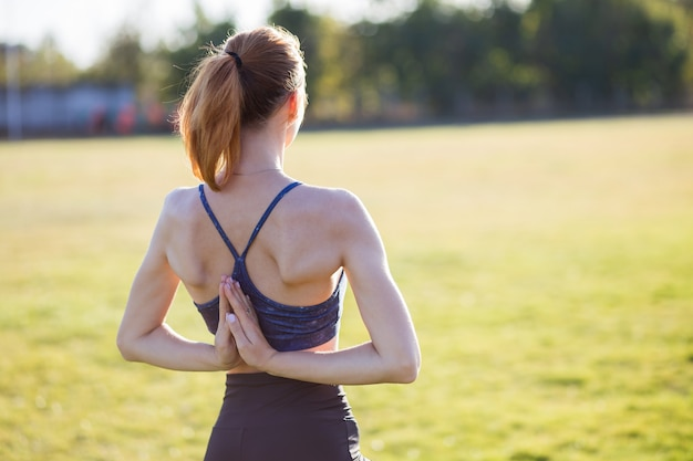 Back view of young girl in yoga position meditates in field