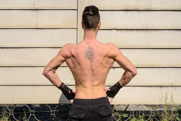 Back view of young handsome fighter man with lean muscular body outdoors