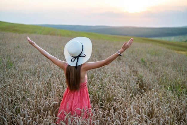 Back view of young happy woman in red summer dress and straw hat standing on yellow farm meadow with ripe golden wheat raising up her hands enjoying warm evening.