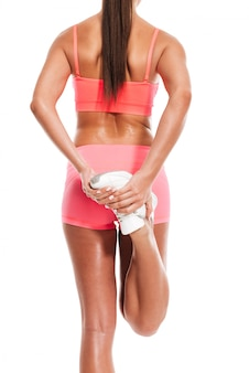 Back view of a young healthy fitness woman stetching legs
