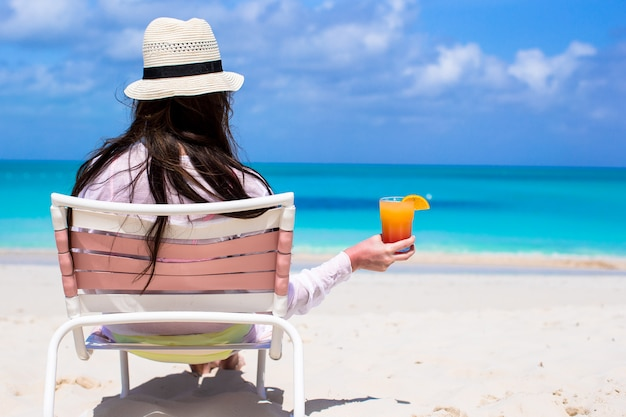 Back view young long haired woman with cocktail in hand and straw hat on beach