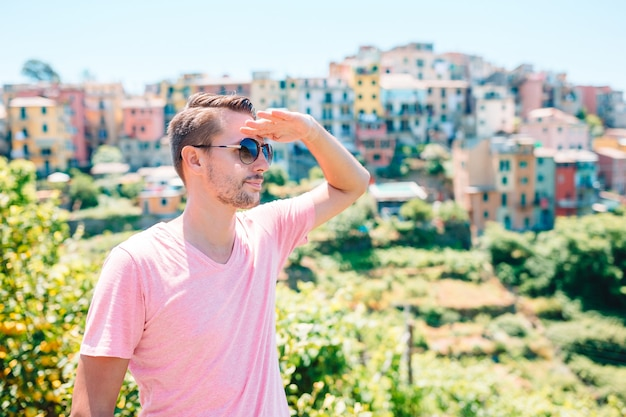 Back view of young man background stunning village. tourist looking at scenic view of manarola