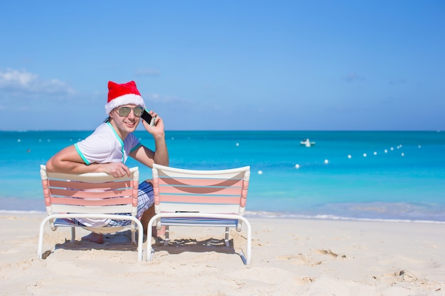 Back view of young man in christmas hat at beach chair