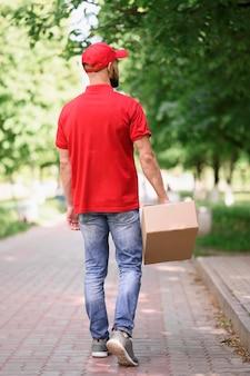 段ボール箱を提供する若い男の背面図