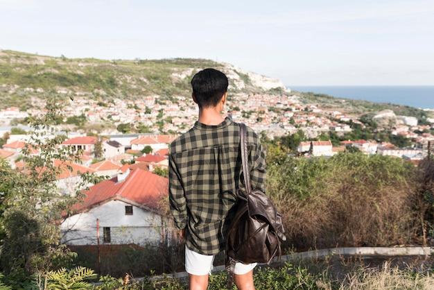 Вид сзади молодой человек, наслаждаясь пейзажем