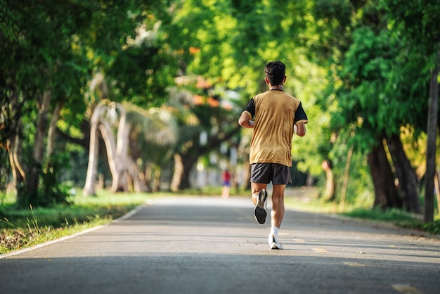 Back view of young man jogging or running exercising outdoors in park, concept of healthy lifestyle.