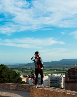 Back view of young man looking at city from castle rooftop. lifestyle and freedom concept.
