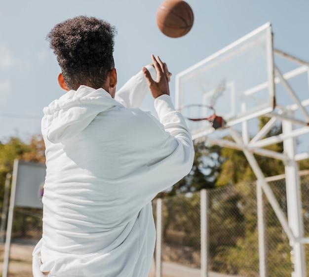 Вид сзади молодой человек играет в баскетбол