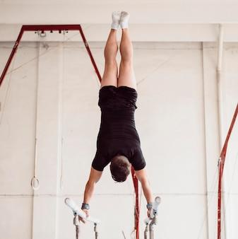 Молодой человек, тренирующийся на брусьях, вид сзади