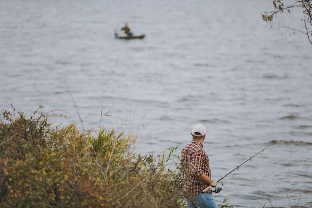 뒷모습 체크무늬 셔츠를 입은 낚싯대를 든 젊은 남자, 모자는 물고기를 잡고 관목과 갈대 근처 해안에서 호수에 있는 보트를 봅니다. 라이프 스타일, 레크리에이션, 어부의 레저 개념