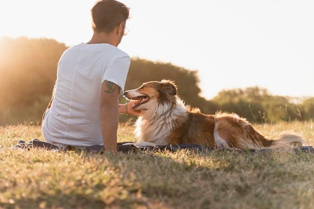 海辺で犬と一緒に若い男を背面図