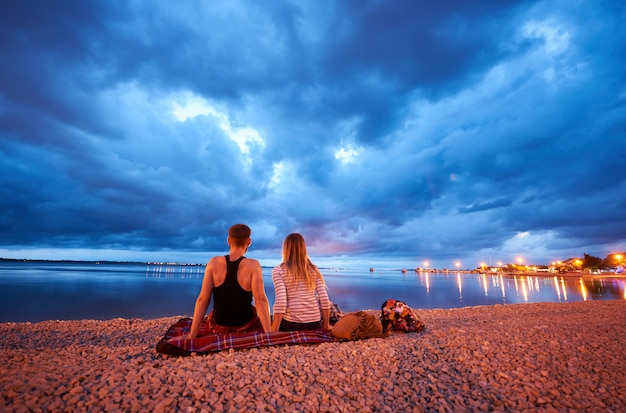 Back view of young man and woman sitting on rug on resort town pebble beach at dusk, enjoying view of cruise boats floating in calm blue water and dramatic cloudy evening sky