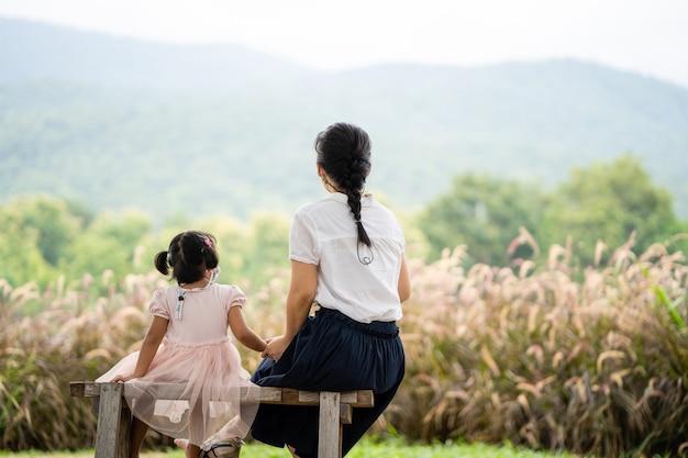 Вид сзади молодая мать и дочь с защитной маской, сидя в парке