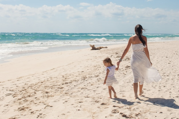 Back view of young mother and her cute daughter walking on exotic beach
