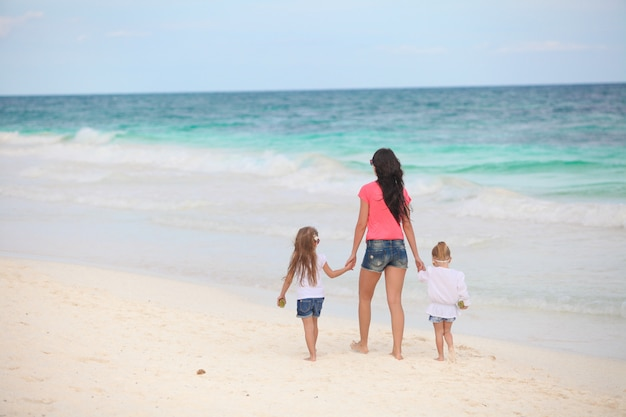 Back view of young mother and her cute daughters walking along the sea
