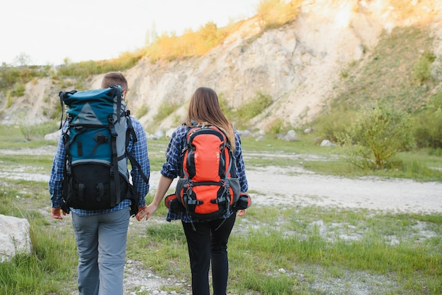 Back view of young pair backpackers with big backpacks holding hands and walking along a road with beautiful mountain