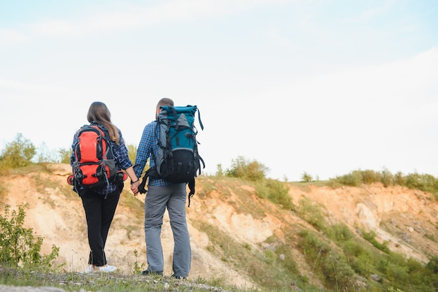 Back view of young pair backpackers with big backpacks holding hands and walking along