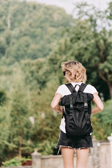 Back view of young pretty woman with short hairstyle with backpack traveling in mountains in sunny good day, trip, adventures, road, relax, holiday