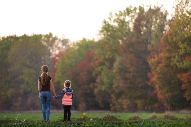 Back view of young slim attractive mother and child girl standing in green meadow