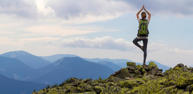 Back view of young slim tourist girl with backpack standing on one leg in yoga pose on rocky top on bright blue morning sky and foggy mountains background. tourism, traveling and climbing concept.
