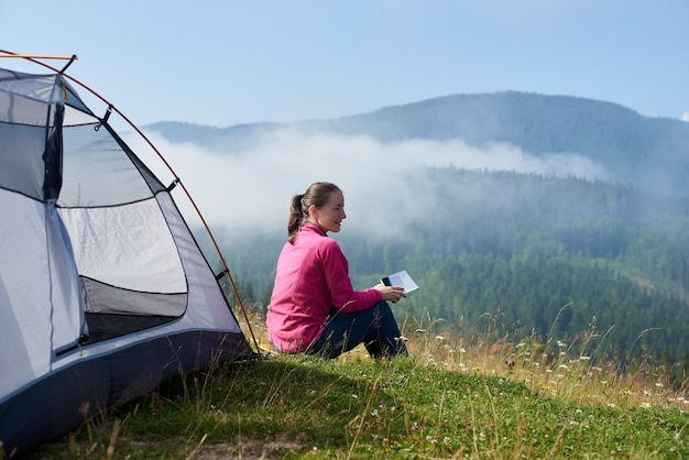 Back view of young smiling tourist woman sitting on green grass of blooming valley at tourist tent, reading a book on bright summer morning on foggy mountains background.