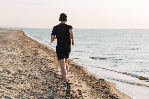 Back view of young sportsman jogging at the beach