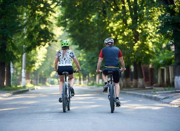Back view of young sporty couple riding bicycles down paved street in green beautiful park