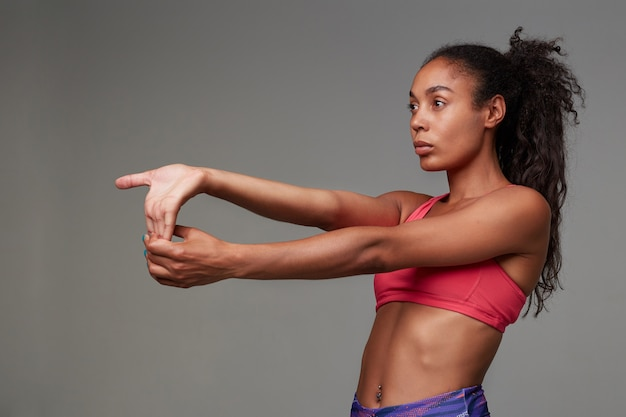 Back view of young sporty dark skinned curly long haired brunette woman stretching her arms after gym, looking in front of her with concentrated face, isolated