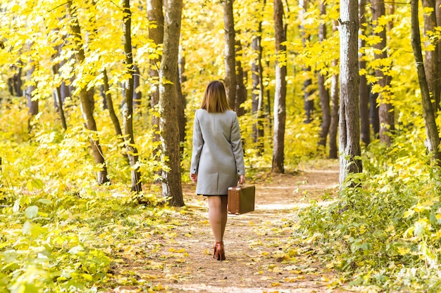 Back view of young stylish woman with retro suitcase walking in autumn park
