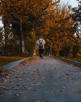 Vista posteriore di una giovane ragazza adolescente che cammina in un parco in una giornata autunnale