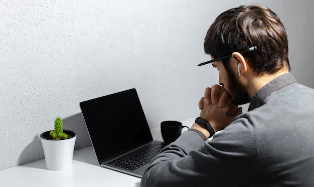 Back view of young thoughtful businessman with pencil on ear, looking in laptop, using wireless earphones, wearing smartwatch, coffee cup and cactus on white desk.