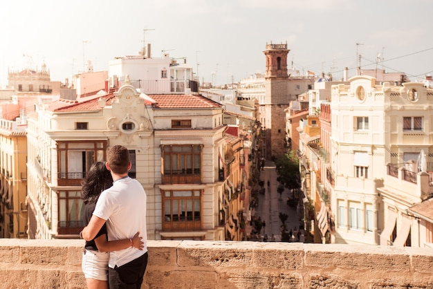 Back view of a young tourist couple looking out at buildings in a city