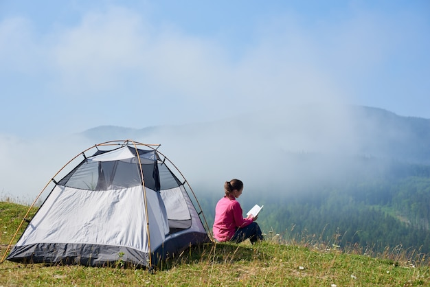 Back view of young tourist girl sitting on green grass of blooming valley at tourist tent under beautiful blue sky reading a book on bright summer morning on foggy mountains