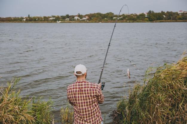 뒷모습 체크무늬 셔츠, 모자, 선글라스를 쓴 면도를 하지 않은 젊은 남자는 관목과 갈대 근처 해안에서 호수에서 잡은 물고기와 함께 낚싯대를 꺼냅니다. 라이프 스타일, 레크리에이션, 어부의 레저 개념.