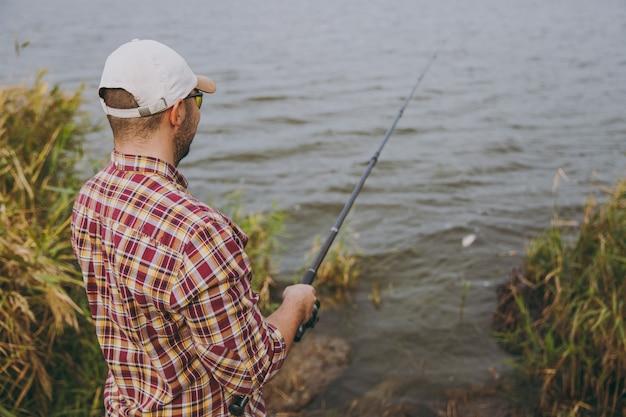 뒷모습 바둑판 무늬 셔츠, 모자, 선글라스를 쓴 낚싯대를 든 면도를 하지 않은 젊은 남자가 미끼를 던지고 관목과 갈대 근처의 호숫가에서 낚시를 합니다. 라이프 스타일, 레크리에이션, 레저 개념입니다.