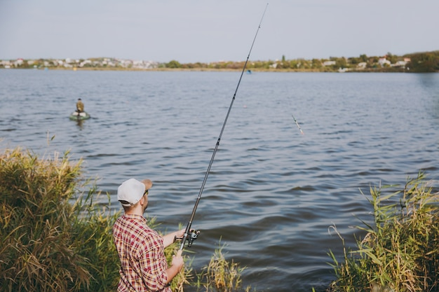 Vista posteriore giovane uomo con la barba lunga con canna da pesca in camicia a scacchi, cappello e occhiali da sole lancia esche e pesca sul lago dalla riva vicino a arbusti e canne. stile di vita, ricreazione, concetto di svago del pescatore.